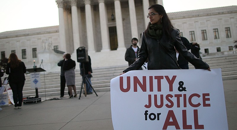 A women holds a sign that reads 'Unity & Justice for All' during a protest in...