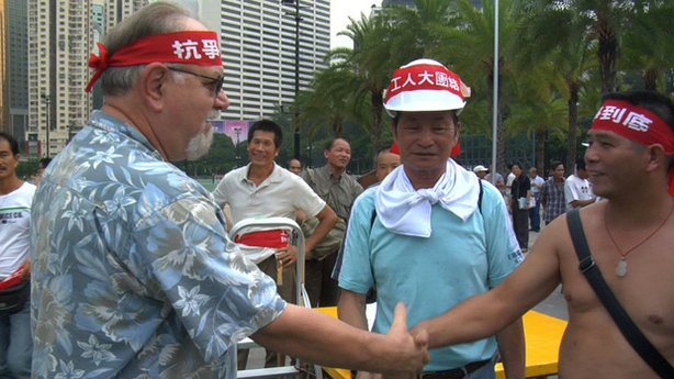 Roy Koch shakes the hand of ironworkers during one of the largest strikes in Hong Kong in the past century.