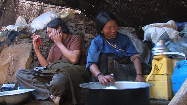 Yama churns butter as Locho attends to his skin care regimen, Zachukha, in ea...