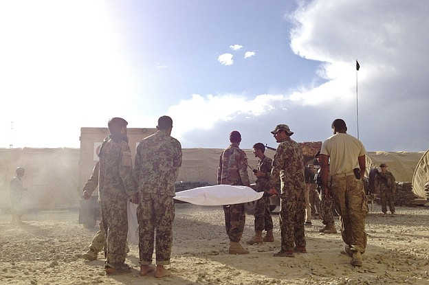 The body of an Afghan soldier is carried to an ambulance in eastern Afghanist...