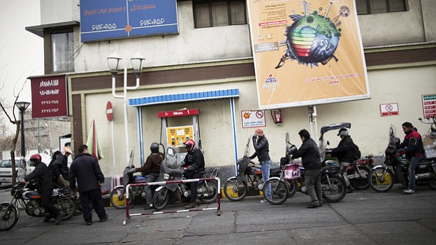Iranians line up at a petrol station to fuel their motorcycles in central Teh...