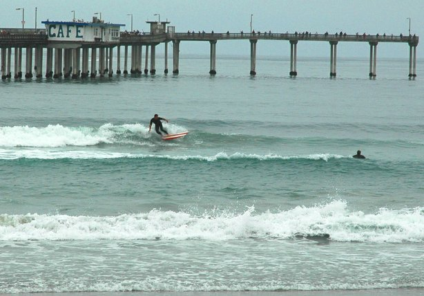 "A surfer in Ocean Beach rides under the ""June Gloom."""