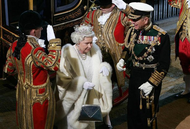 Queen Elizabeth II and the Duke of Edinburgh (right, in black uniform) arrive by royal carriage at the House of Lords in London for the state opening of Parliament.