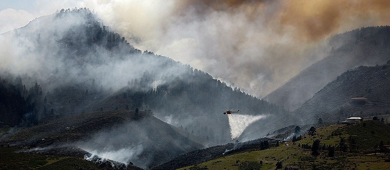 A Sikorsky S-64 Aircrane firefighting helicopter drops water on a hotspot bur...