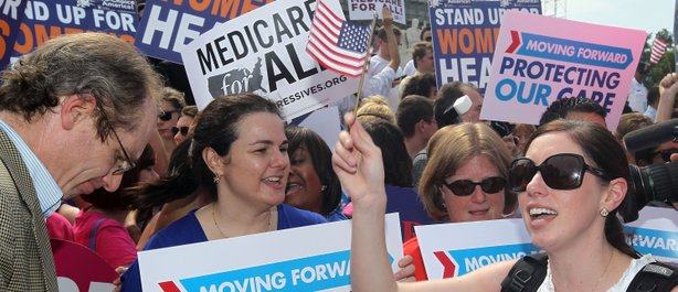 Local resident Angela Botlicella (R), along with other Obamacare supporters, ...