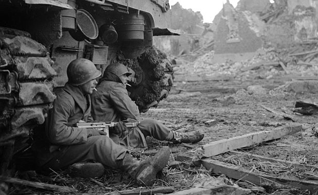 Two soldiers in Geich, Germany, pause for a cigarette behind a tank on Decemb...