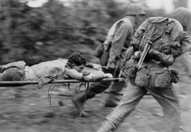 Soldiers transport a wounded man, Okinawa, 1945.