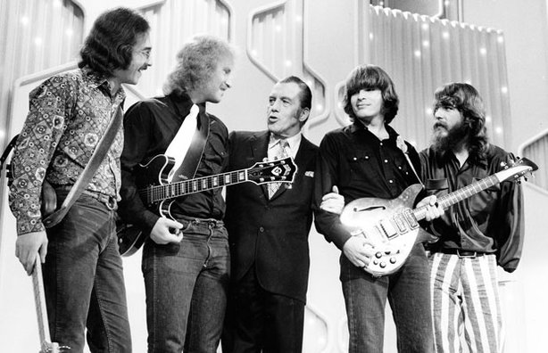 "Creedence Clearwater Revival on stage with Ed Sullivan (Center). ""Proud Mary"" by Creedence Clearwater Revival is one of many classic rock hits featured in this special."