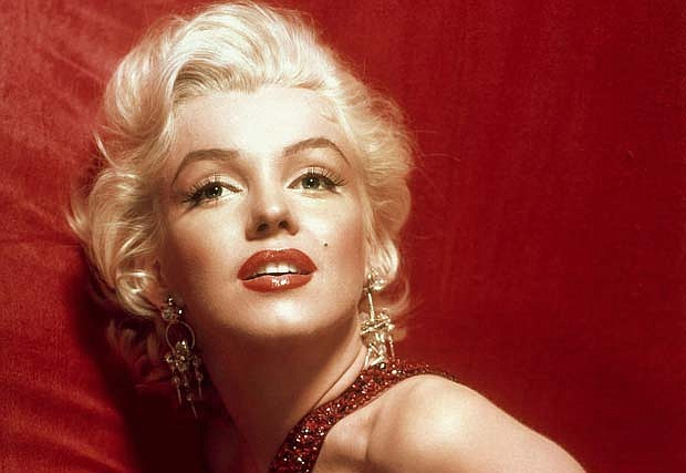 A glamorous Marilyn Monroe in a red dress, photographed by Sam Shaw.