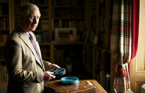 The Prince of Wales with the box of The Queen's cine films is in the Library ...