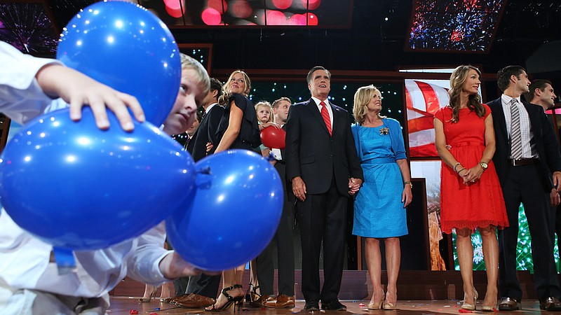 Mitt and Ann Romney (center) are surrounded by family members and balloons at...