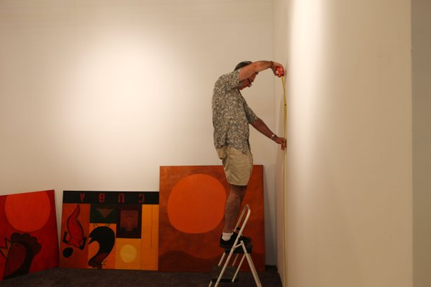 """Pelayo """"Pete"""" Garcia takes measurements in order to hang his paintings at the..."""