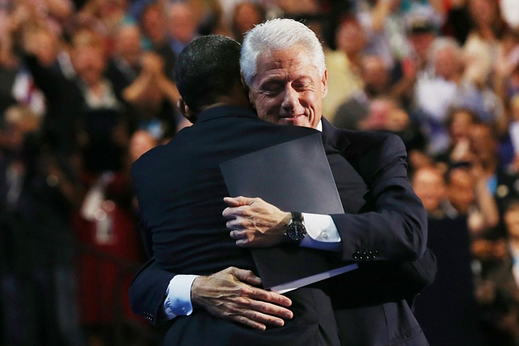 Former President Bill Clinton hugs President Obama onstage after Clinton's ro...