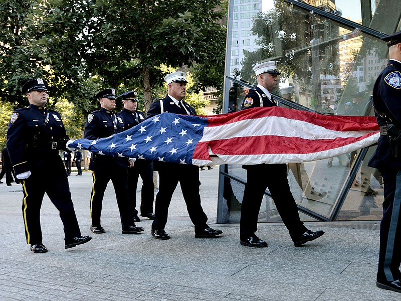 Port Authority Police Officers carry an American flag that flew over at the W...