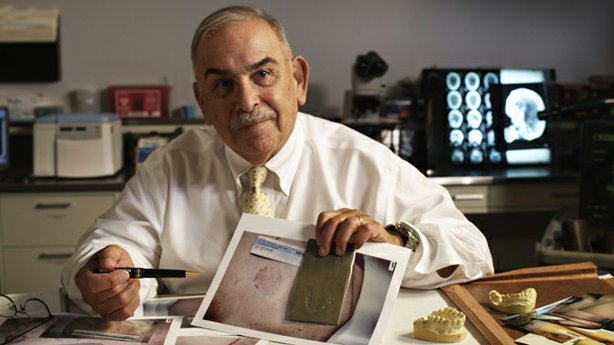 Dr. Lowell Levine, an odontologist at the New York State Police Forensics Services Unit, compares a mold of Roy Brown's teeth to photos of bite marks from the autopsy of Sabina Kulakowski.