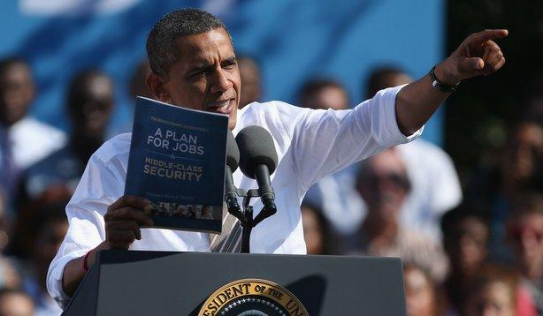 "President Obama holds a copy of ""The New Economic Patriotism: A Plan for Jobs..."