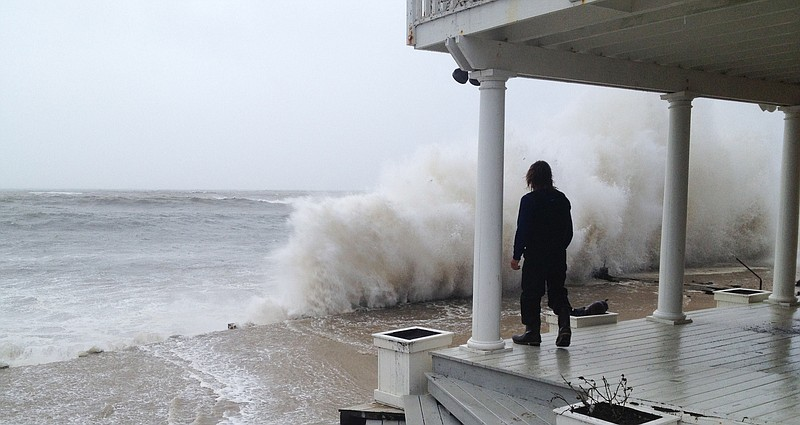 A wave crashes against the shore while person stands on a porch as Hurricane ...