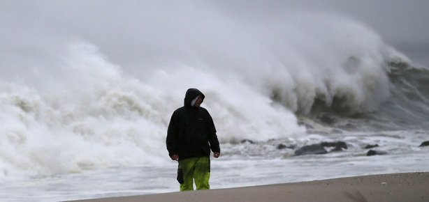 A man stands on the beach as heavy surf from Hurricane Sandy pound the shoreline, on October 29, 2012 in Cape May, New Jersey.