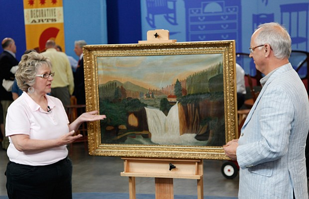 Appraiser Ken Farmer examines a painting with a guest on