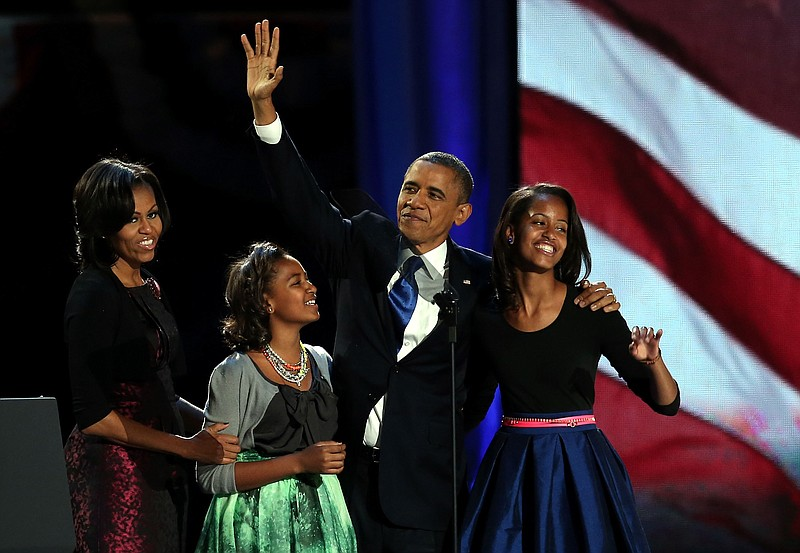U.S. President Barack Obama walks on stage with first lady Michelle Obama and...