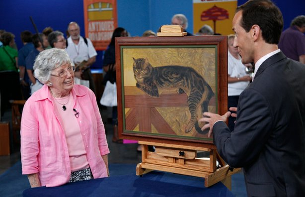 Appraiser Todd Weyman (right) with a guest and her cat portrait.
