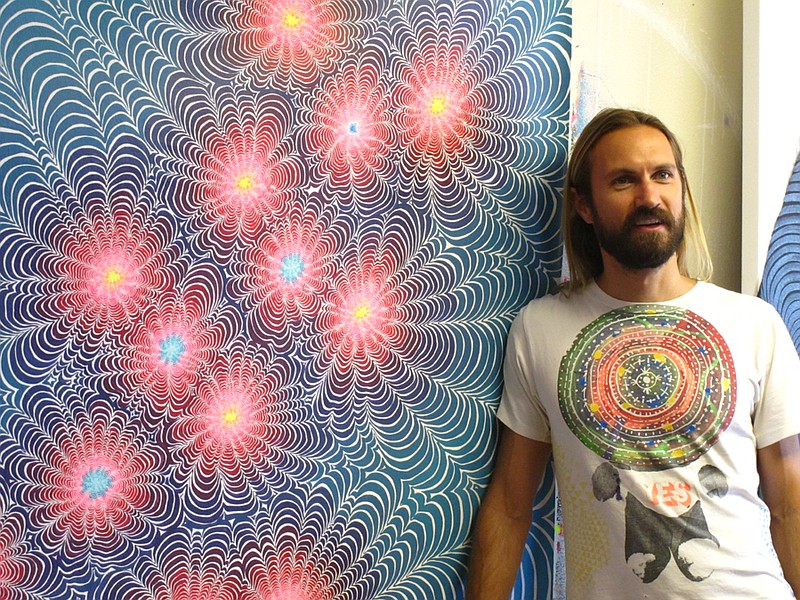 San Diego-based artist Kelsey Brookes in his studio standing next to his pain...