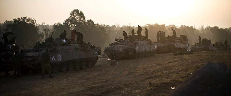 Israeli soldiers prepare weapons and vehicles in a deployment area as the con...