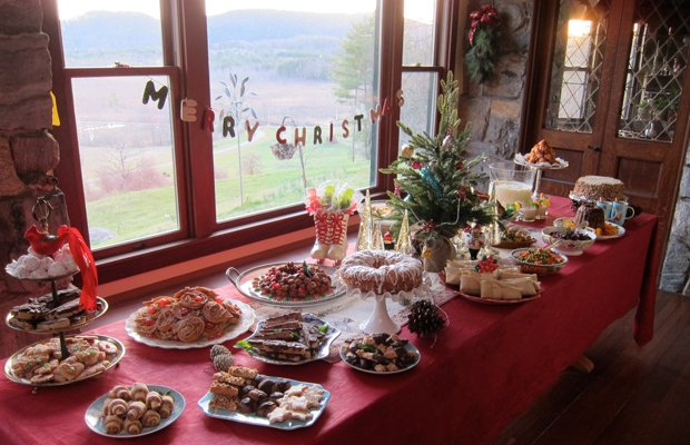 A decorated table loaded up with a small Christmas tree, holiday treats inclu...