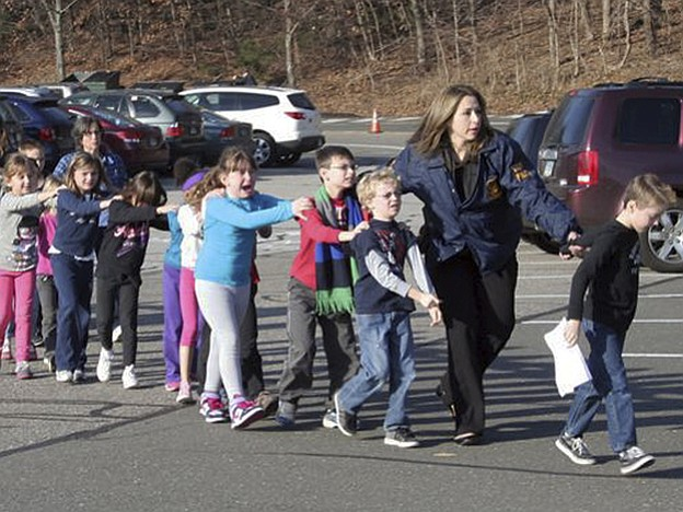 In this photo provided by the Newtown Bee, Connecticut State Police lead chil...