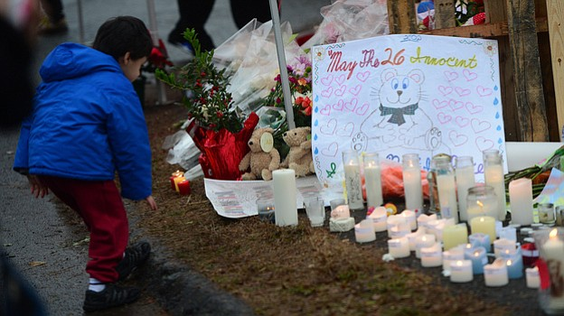 A makeshift shrine honors the victims of a elementary school shooting that ha...
