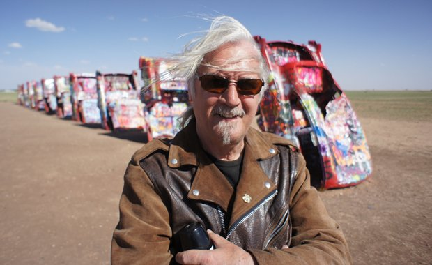 Billy Connolly stands in front of brightly painted cars at Cadillac Ranch, a ...