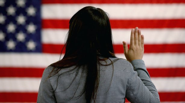 A woman takes the oath of allegiance during a naturalization ceremony at the ...