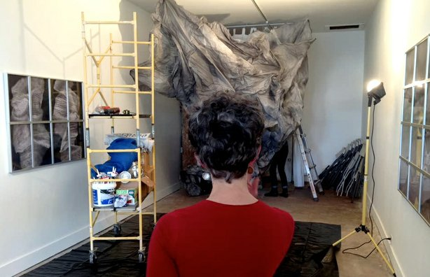 Artist Joyce Dallal surveys the installation of her paper sculpture Media Storm at the Protea Gallery.