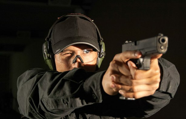 A firearms instructor at F6 Labs in Hicksville, New York, firing a Glock.