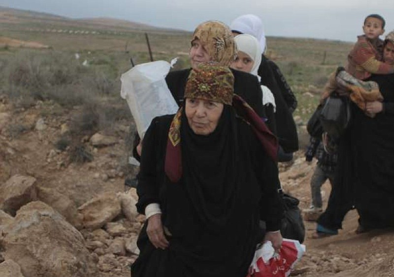 A line of Syrian refugee women, some carrying children, cross into Jordan fro...