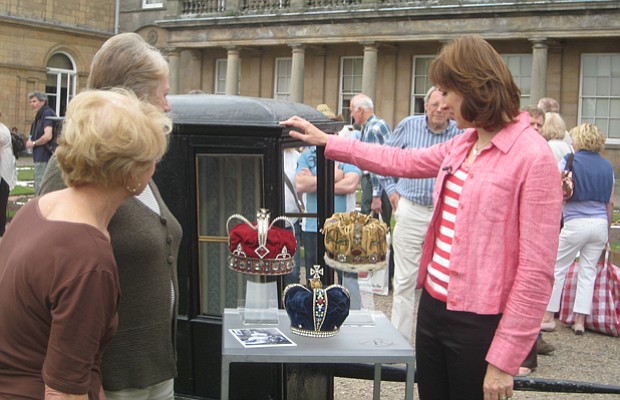 ANTIQUES ROADSHOW host Fiona Bruce examines a sedan chair and some crowns.