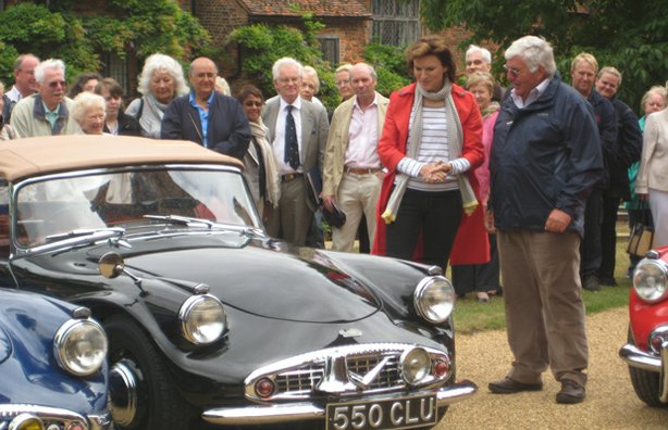 Presenter Fiona Bruce examines a row of classic Daimler Dart cars.