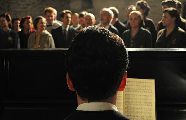 Re-enactment of Raphel Schächter playing piano in front of the Terezin Choir during a rehearsal.