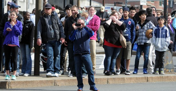 People look on after two bombs exploded during the 117th Boston Marathon on ...
