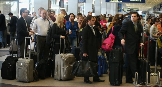American Airlines passengers wait in line at O'Hare Airport in Chicago, Illi...