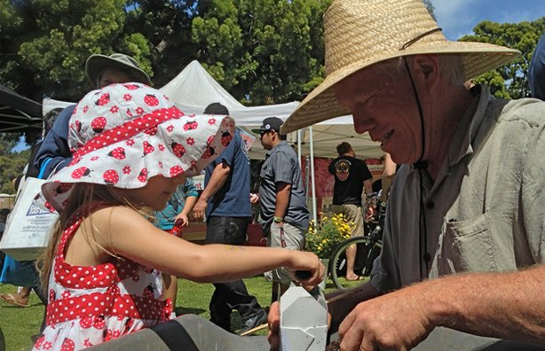 A young participant learns about gardening with Michael Gerdes, director of photography for A GROWING PASSION, at Earth Fair 2013.