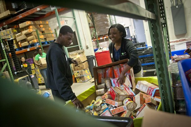 TD Bank volunteers sort donated food into barrels at the Manna Food Center in...