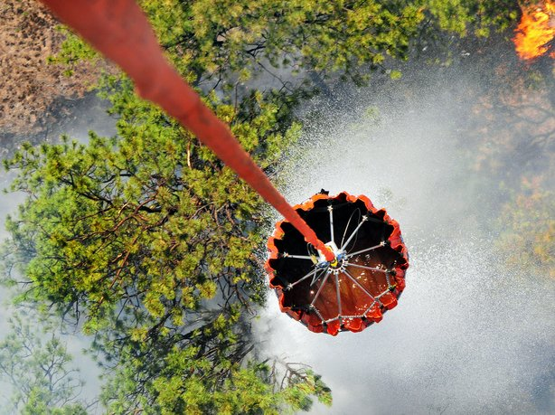 A U.S. Army helicopter releases water onto the Black Forest fire outside Colo...