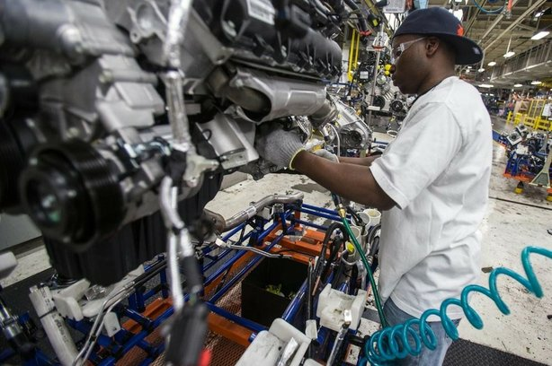 A worker installs parts on a Chrysler SUV engine at the Jefferson North Assem...