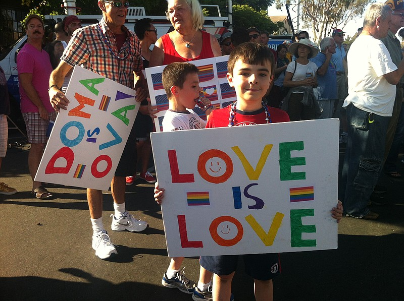 A young child holds a signs supporting same-sex marriage at a post-Supreme Co...