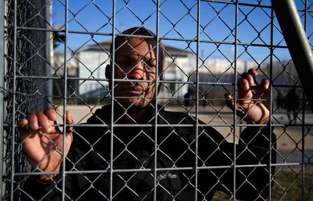 Dieudonné looks through the fence at Frambois detention center.