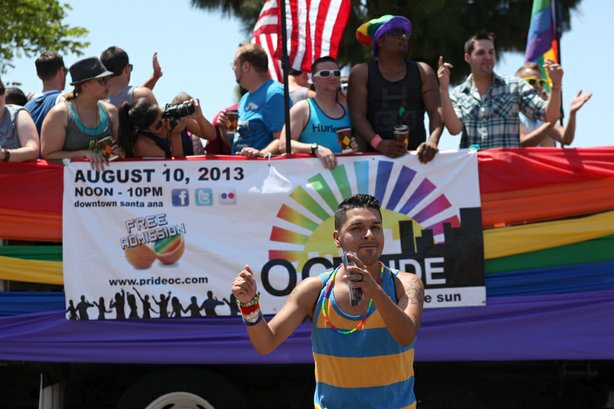 A San Diego Pride Parade participant dances alongside a float on University A...