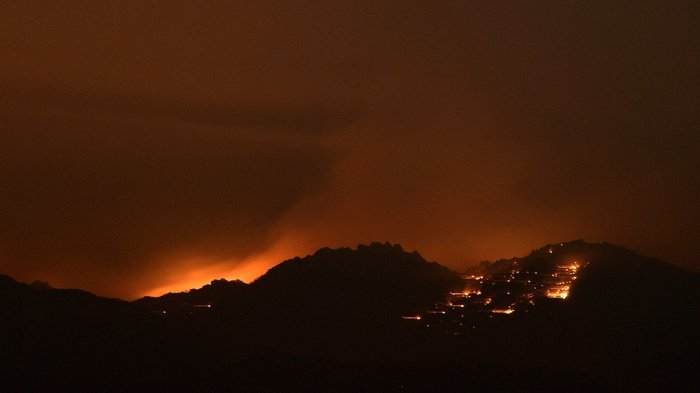 Fire lights the sky near Idyllwild, Calif., early Thursday. Flames have sprea...