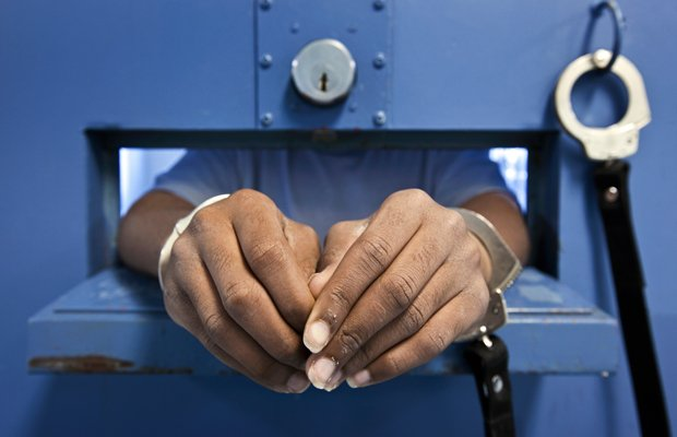 A young offender in handcuffs.