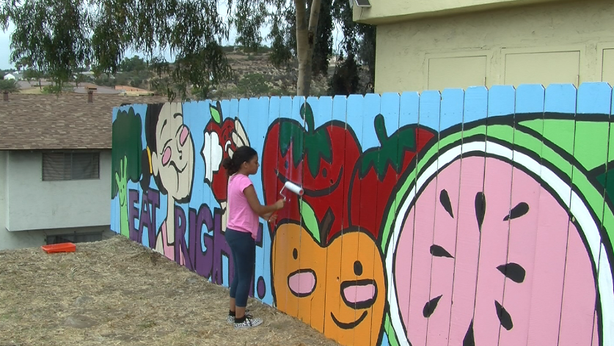 Volunteer Kianna Collins helps cover a new mural near Market Creek Plaza with...